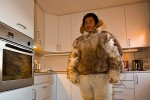Inuit hunter in traditional clothing, in his modern kitchen
